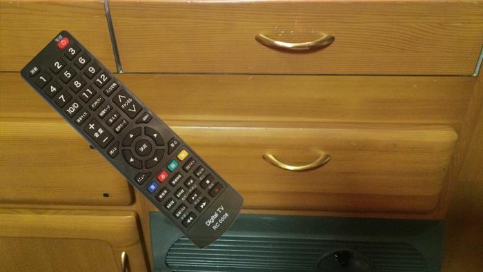 車内冷蔵庫上の引き出しに入っているテレビのリモコンを取り出します。